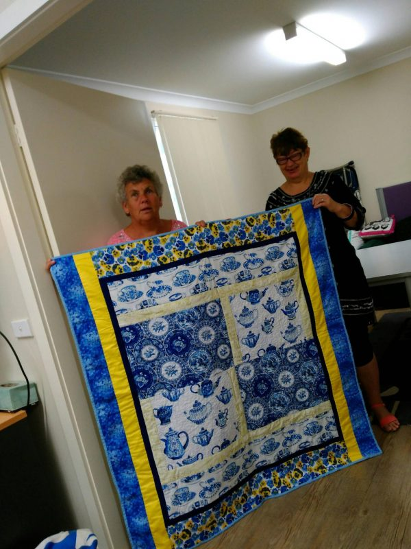 Dearnne Callaghan and Karen Willis holding up the quilt that was donated to Cedar Cafe.