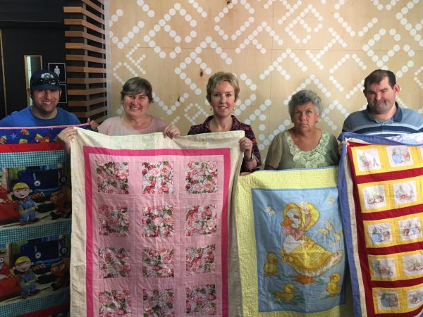 Jye Jeffery, Cherie Lovett, Rebecca Walsh (Ronald McDonald House Executive Officer), Dearnne Callaghan and Shannon Miller with the quilts they made at CDS for the donation.
